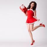 Frau im roten Weihnachtsreizvollen Kostümsprung mit Geschenk stockbild
