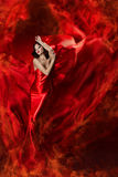 Frau im roten wellenartig bewegenden Kleid als Feuerflamme Stockfotos