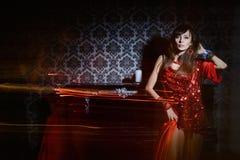 Frau im roten wellenartig bewegenden Kleid im Innenraum stockfotos