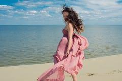 Frau im roten wellenartig bewegenden Kleid mit Fliegengewebe läuft auf Hintergrund von Dünen Skyline und das Meer Lizenzfreies Stockfoto