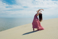 Frau im roten wellenartig bewegenden Kleid mit Fliegengewebe läuft auf Hintergrund von Dünen Turner auf der Rückseite der Düne Stockfotografie
