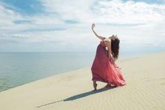 Frau im roten wellenartig bewegenden Kleid mit Fliegengewebe läuft auf Hintergrund von Dünen Turner auf der Rückseite der Düne Lizenzfreie Stockbilder