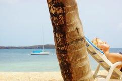 Frau im Ruhestand, die auf dem Strand ein Sonnenbad nimmt Stockbild