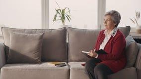 Frau im Ruhestand, die auf Sofa herein im Wohnzimmer mit großem Fenster sitzt und Tagebuch schreibt stock video