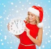 Frau im Sankt-Helferhut mit der Uhr, die 12 zeigt Lizenzfreies Stockfoto