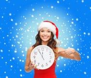Frau im Sankt-Helferhut mit der Uhr, die 12 zeigt Lizenzfreie Stockbilder