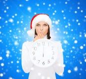 Frau im Sankt-Helferhut mit der Uhr, die 12 zeigt Stockfotos