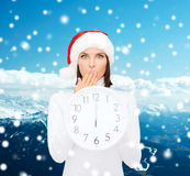 Frau im Sankt-Helferhut mit der Uhr, die 12 zeigt Stockbild
