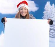 Frau im Sankt-Hut, der das sehr große Zeichenlächeln anhält Lizenzfreies Stockfoto