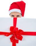 Frau im Sankt-Hut, der hinter Weihnachtsgeschenk sich versteckt Stockfotografie