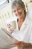 Frau im Schlafzimmer mit dem Kaffee- und Zeitungslächeln lizenzfreie stockbilder