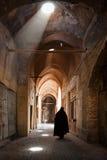 Frau im Schleier, der durch großartigen alten Basar von Yazd überschreitet Stockbild
