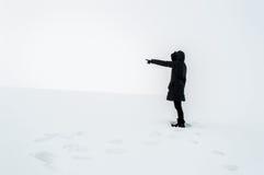Frau im Schnee ihren Finger in Richtung zur Leerstelle zeigend Lizenzfreie Stockbilder