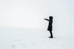 Frau im Schnee ihren Finger in Richtung zur Leerstelle zeigend Stockbilder