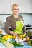 Frau im Schutzblech an der Küche Lizenzfreies Stockbild