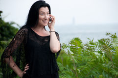 Frau im Schwarzen auf Mobiltelefon durch das Meer lizenzfreie stockbilder