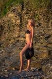 Frau im schwarzen Bikini, der auf einem Sand aufwirft, schaukelt Lizenzfreie Stockfotografie