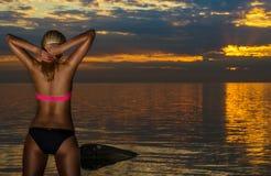 Frau im schwarzen Bikini, der auf einem Sand aufwirft, schaukelt Stockfotos