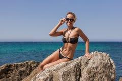 Frau im schwarzen Bikini und abgetönten in der Sonnenbrille, die auf Felsen stützt Lizenzfreie Stockbilder