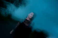Frau im Schwarzen eingehüllt in Dunkelheit und in Geheimnis Stockfotografie