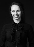 Frau im schwarzen Hemd mit hellem Lippenstift und breitem Lächeln Stockbild