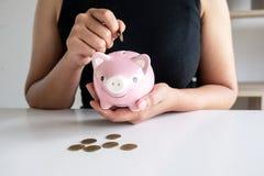 Frau im schwarzen Hemd unterrichten Ausrüstungen zum Einsetzen der Münze in rosa Sparschwein lizenzfreies stockfoto