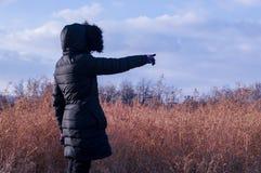 Frau im Schwarzen ihren Finger in Richtung zur Leerstelle zeigend Stockbilder