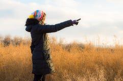Frau im Schwarzen ihren Finger in Richtung zur Leerstelle zeigend Lizenzfreie Stockfotografie