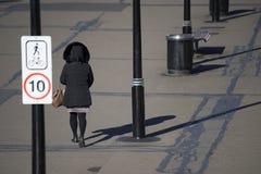 Frau im schwarzen Jackenmantel gehend von der Rückseite Stockfotografie