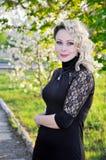 Frau im schwarzen Kleid über Frühlingsobstgarten Lizenzfreie Stockfotografie