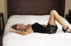 Frau im schwarzen Kleid, das auf Bett liegt stockfotos