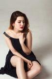Frau im schwarzen Kleid, das auf Boden sitzt Lizenzfreie Stockfotografie