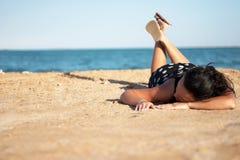 Frau im schwarzen Kleid, das auf Strand sich entspannt stockfotos