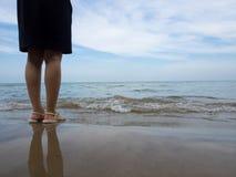 Frau im schwarzen Kleid, das auf Strand steht Lizenzfreie Stockfotografie