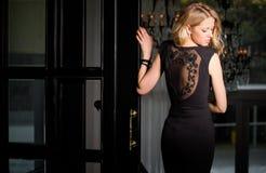 Frau im schwarzen Kleid mit dem hinteren Schauen der Spitzes über Schulter Stockbild