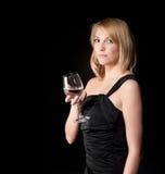 Frau im schwarzen Kleid mit Glas über dunklem Hintergrund Lizenzfreie Stockfotografie