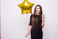 Frau im schwarzen Kleid mit trinkendem Champagner des sternförmigen Ballons Stockbild