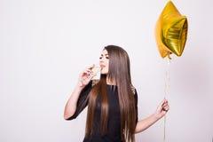Frau im schwarzen Kleid mit trinkendem Champagner des sternförmigen Ballons auf Weiß Lizenzfreie Stockbilder