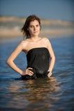Frau im schwarzen Kleid am Strand, der naß erhält Lizenzfreies Stockfoto