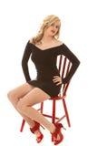 Frau im schwarzen Kleid und in den roten Schuhen auf rotem Stuhl Lizenzfreies Stockbild
