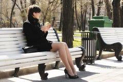 Frau im Schwarzen mit Apfel auf Bank lizenzfreie stockbilder