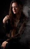Frau im Schwarzen mit Rauche Lizenzfreie Stockfotografie