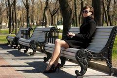 Frau im schwarzen Oberen, das auf Bank sitzt stockbild