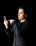 Frau im Schwarzen unter Verwendung des Handys Stockfoto