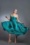Frau im Seidenkleid, das auf Wind wellenartig bewegt Fliegender und flatternder Kleiderstoff über grauem Hintergrund Lizenzfreie Stockfotos