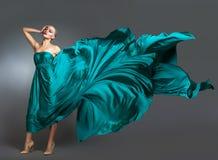 Frau im Seidenkleid, das auf Wind wellenartig bewegt Fliegender und flatternder Kleiderstoff über grauem Hintergrund Stockbild
