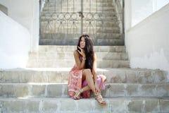 Frau im Sommerkleid, das auf den Steinschritten sitzt Stockfotografie