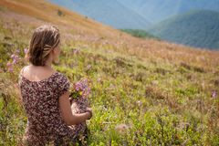 Frau im Sommerkleid mit Blumen Bergblick genießend Vacat Lizenzfreies Stockfoto