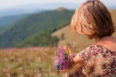 Frau im Sommerkleid mit Blumen Bergblick genießend Vacat Stockfotos