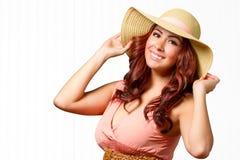 Frau im Sommerkleid mit den Händen auf Hut Lizenzfreie Stockfotos